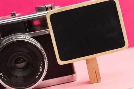 A photo camera with a little blackboard on a pink background