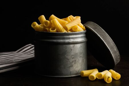 Raw macaroni in a galvanized can on a dark background Stockfoto