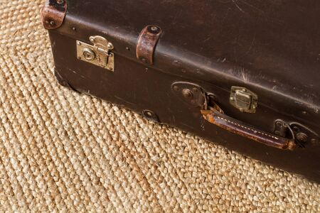 A vintage leather suitcase on a esparto carpet