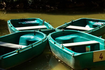 Four green boats in a pond