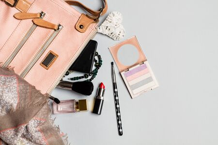 Blushes, brushes and a lipstick for make up beside a handbag 版權商用圖片