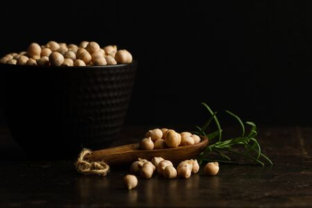 Chickpeas in a black ceramic bowl and in a wooden spoon on a dark background