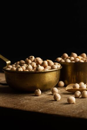 Raw chickpeas in spoons on a wooden kitchen board on a dark background