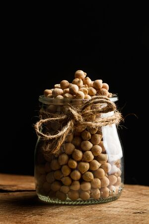 Raw chickpeas in a crystal jar on a dark background