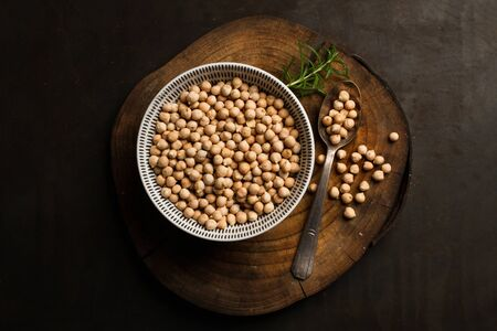 Raw chickpeas in a ceramic bowl on a wooden kitchen board on a black bachground Stock Photo