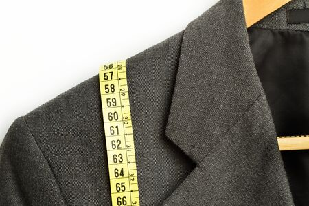 Yellow measuring tape on a gray suit