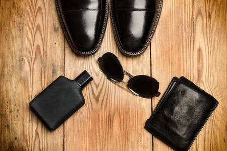 Black shoes, sunglasses and a wallet on a wooden table Фото со стока