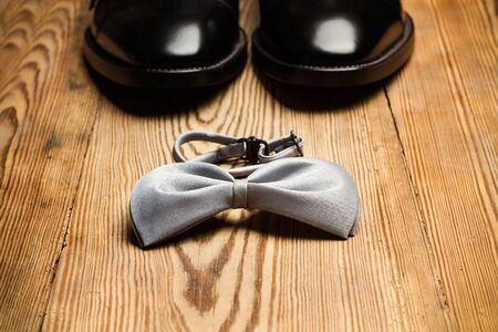 Black shoes and a gray bow tie on a wooden table Фото со стока