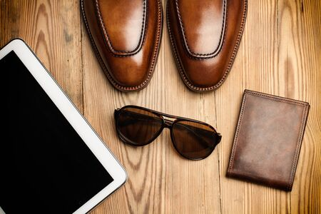 Brown shoes, sunglasses and a tablet on a wooden table