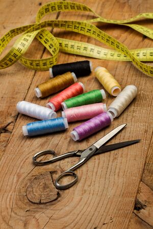 Sewing thread spools and sewing accessories on a wooden table Фото со стока