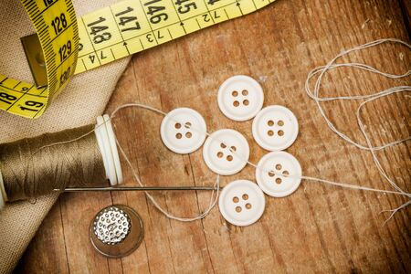 Sewing thread, plastic buttons and sewing accessories on a wooden table