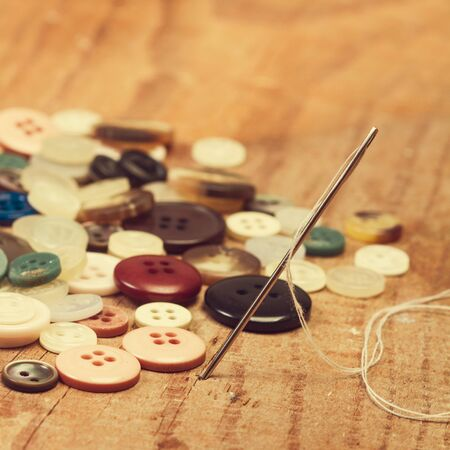 Sewing needle and buttons on a wooden table