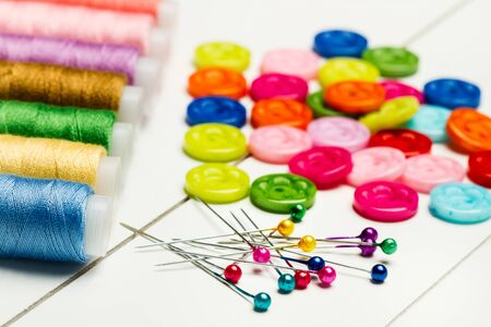 Sewing pins, sewing threads and colored buttons on a white table