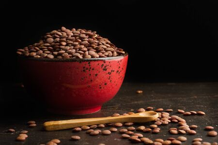 Lentils in a red bowl on a dark background