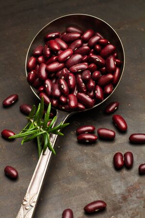 Raw red beans in a ladle on rusty table Фото со стока