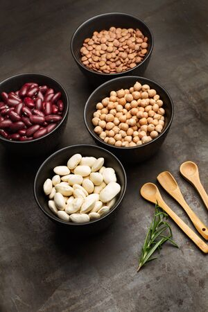 Beans, lentils and chickpeas in black bowls with wooden spoons