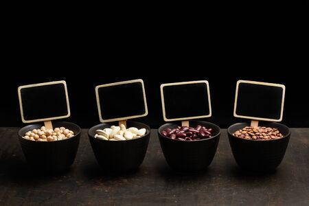 Beans, lentils and chickpeas in black bowls on a dark background Фото со стока