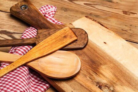 Wood kitchenware on a wooden table with a checkered napkin