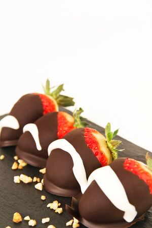 Strawberries with chocolate on a black slab