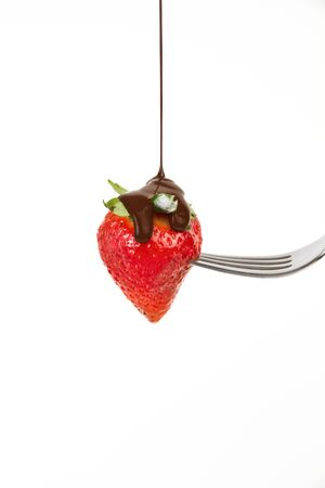 a strawberry punctured on a fork covered with chocolate syrup Фото со стока