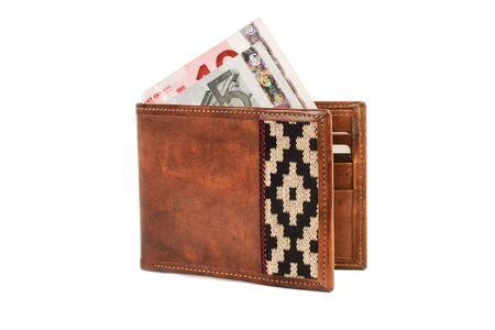 A leather wallet and banknotes on a white background.