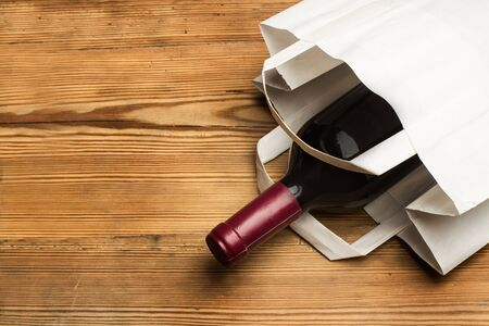 Bottle of red wine in a paper bag