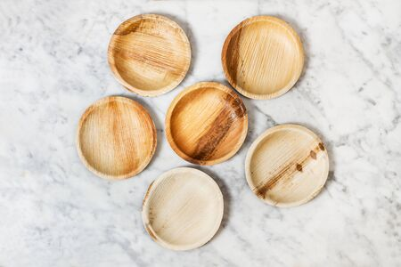 Small wooden plates on a marble table Фото со стока