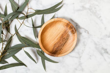 Small wooden plate on a marble table