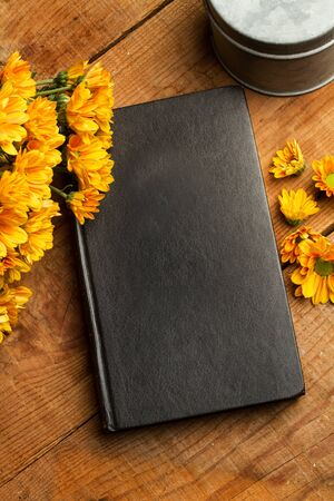 A book and marguerites on a wooden table