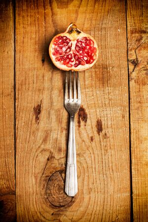 Pomegranate with a fork on a wooden table Stok Fotoğraf - 130599633