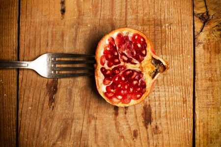 Pomegranate with a fork on a wooden table