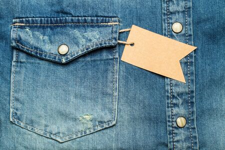 A blue jean shirt with a label in the pocket