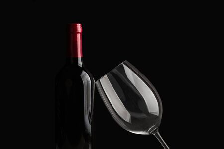 A bottle of red wine and a glass on a dark background