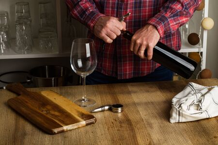 Man opening a glass of red wine on a wooden table