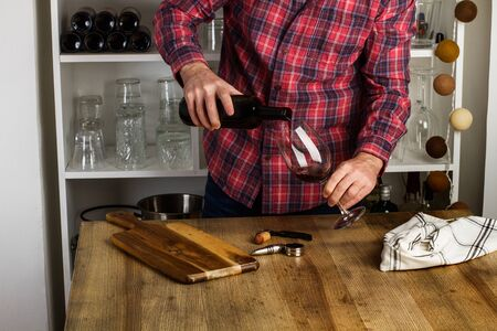 Man serving a glass of wine on a wooden table