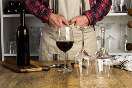 Man standing in front of wooden table with a glass of wine on it 스톡 콘텐츠