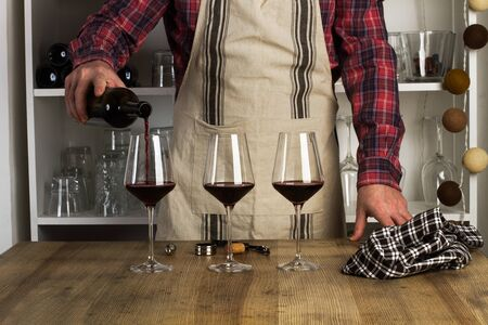 Man with an apron serving a glass of red wine