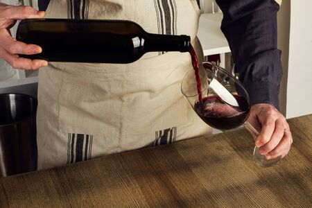 Man met een schort die een glas rode wijn serveert