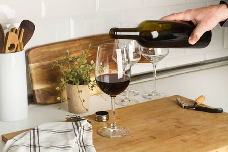 Man serving a glass of red wine in the kitchen