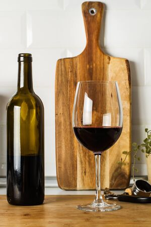 A bottle of red wine and a glass on a wooden board on the kitchen counter 스톡 콘텐츠