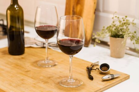 A bottle of red wine and two glasses on a wooden board on the kitchen counter 스톡 콘텐츠