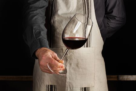 A man with an apron and a glass of red wine in his hand 스톡 콘텐츠