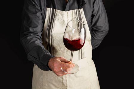 Un uomo con un grembiule e un bicchiere di vino rosso è in mano