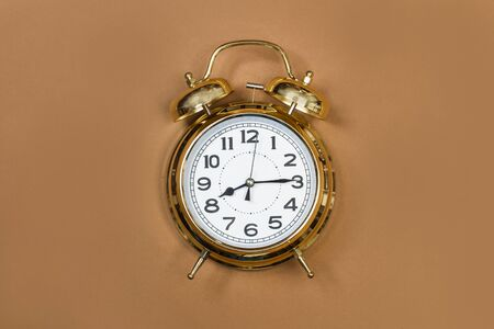 Old alarm clock on a brown background