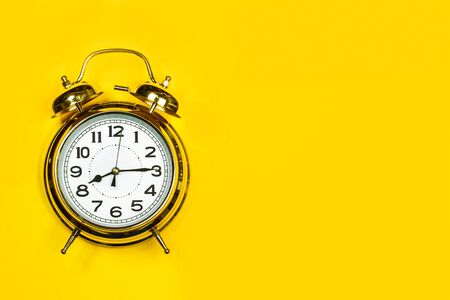 Old alarm clock on a yellow background