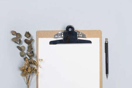 A clipboard table with paper and a pencil on a gray background