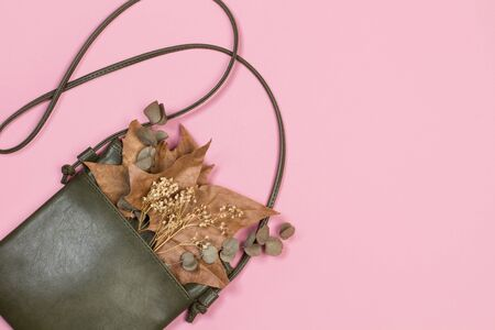 A leather handbag with dry leaves on a pink background