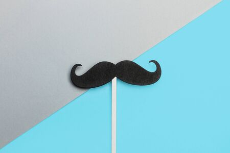 A black mustache on a gray and blue background