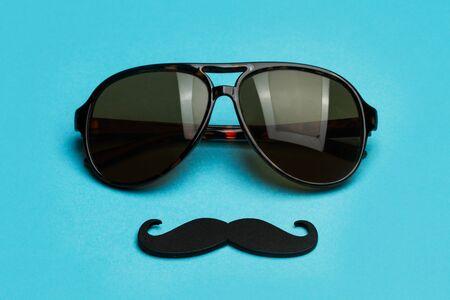 Sunglasses and a black mustache on a blue background Stok Fotoğraf