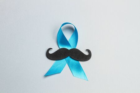 A blue ribbon and a black mustache on a gray blackground